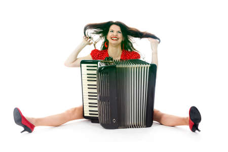 pretty woman in red has fun with accordion on floor of studio with white background Stock Photo
