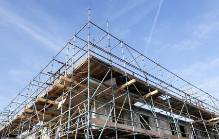 scaffolding on building site of new apartment building and blue sky in the netherlands