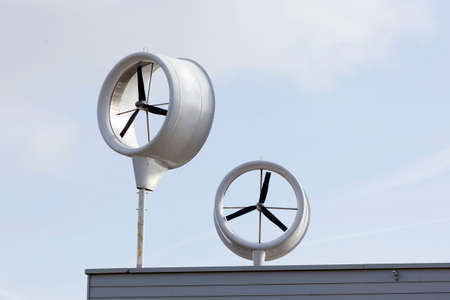 air pressure: urban windmill on roof of new building in the netherlands and blue sky