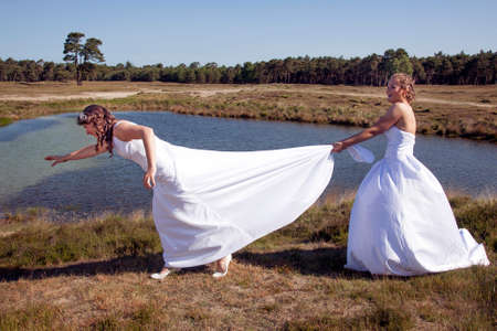 just married happy lesbian couple in white dress has fun near small lake and forest on sunny day Stock Photo