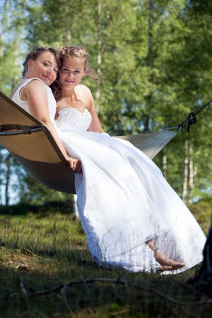 two just married brides pose on hammock in forest on sunny summer day Stock Photo