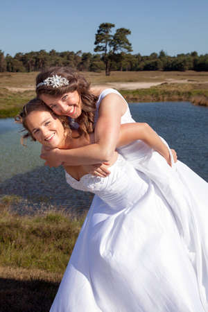 just married happy lesbian couple in white dress embrace and make fun near small lake and forest on sunny day