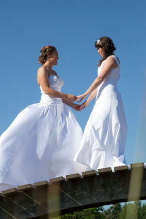 two just married brides in white dress pose on wooden bridge in forest on sunny summer day Stock Photo
