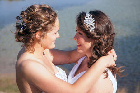just married happy lesbian couple in white dress look each other happily in the eyes near small lake and forest on sunny day Stock Photo