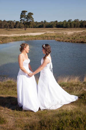 just married happy lesbian couple in white dress near small lake and forest on sunny day