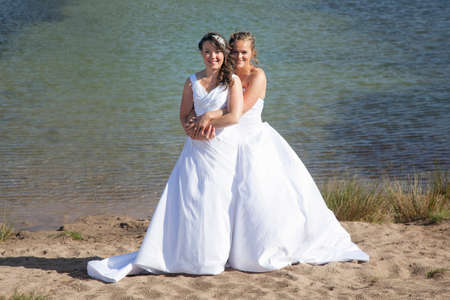 just married happy lesbian couple in white dress embrace near small lake and forest on sunny day
