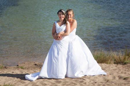 net getrouwd gelukkig lesbisch paar in witte jurk omarmen in het buurt van klein meer en bos op zonnige dag