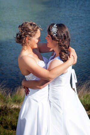 affections: just married happy lesbian couple in white dress look each other happily in the eyes near small lake on sunny day