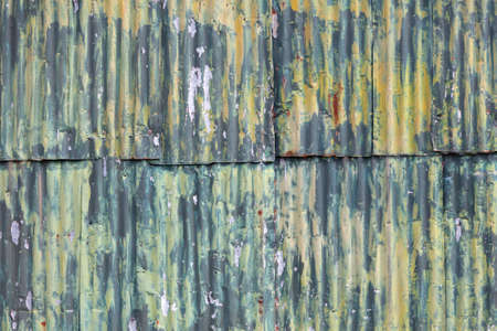 shed: horizontal picture of rusty corrugated iron wall of she with green yellow paint