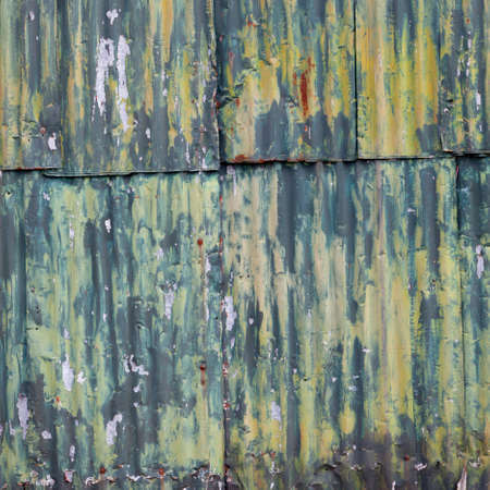 shed: square picture of rusty corrugated iron wall of she with green yellow paint