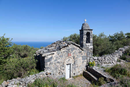 very old stone church ekklesia agios nicolaos on mani in greek peloponnese with blue sea and sky on sunny day in spring Stock Photo