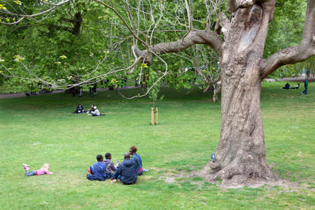 picknick: London, United Kingdom, 6 may 2017: family sits on the grass of london st jamess park on spring day near large old tree