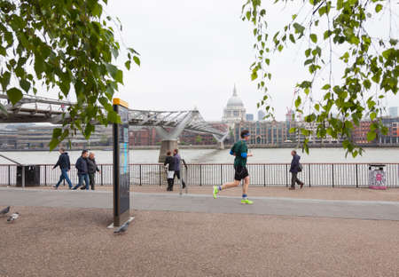 st pauls: London, United Kingdom, 6 may 2017: people walk and jog near millennium bridge along river thames in london on overcast day in spring