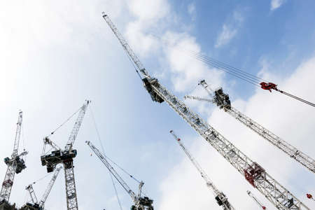 lot of cranes on building site as colorful sihouettes against blue sky and clouds in the centre of london