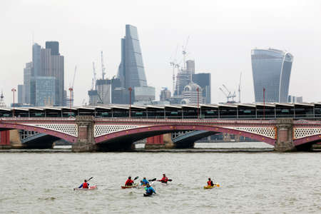 London, United Kingdom, 6 may 2017: people canoeing on river thames in london look at london city skyline behind blackfriars bridge on overcast day in spring