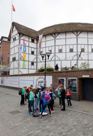 globe theatre: London, United Kingdom, 6 may 2017: group of teenagers stands in front of shakespeares globe theatre on southbank of river thames in london