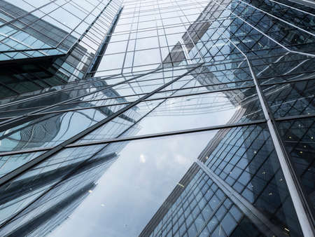 abstract pattern of lines and sky reflecting glass facades of modern steel corporate building