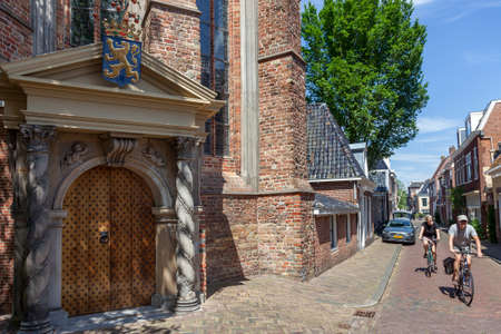 Leeuwarden, Netherlands, 11 june 2017: couple on bicycle pass the orange porch of the large or Jacobin church in leeuwarden