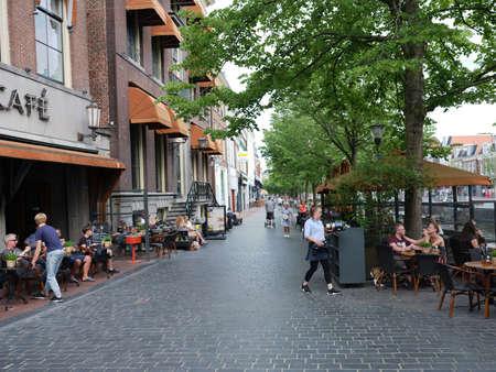 Mensen genieten van een drankje in het buitencafé in het centrum van de oude stad Leeuwarden in Friesland op de lentedag