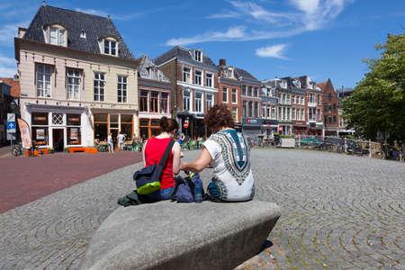 leeuwarden, nederland, 11 juni 2017: twee vrouwen zitten op grote steen op brug in het centrum van de oude stad leeuwarden met terras op de achtergrond op zonnige dag in de vroege zomer