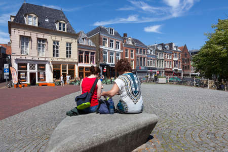 leeuwarden, netherlands, 11 juni 2017: two women sit on large stone on bridge in centre of old city leeuwarden with outdoor cafe in the background on sunny day early summer