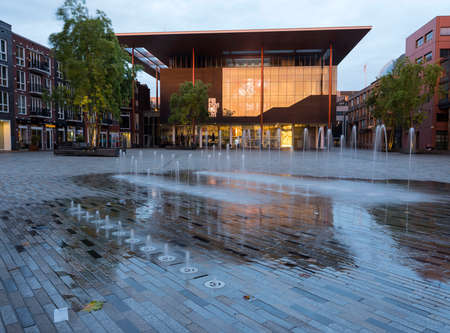 Modern fries museum at dusk in center of old province capital leeuwarden of friesland in the netherlands with reflections in water of fountain