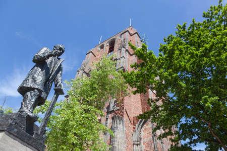 standbeeld van troelstra naast oldehove toren in het centrum van leeuwarden, hoofdstad van friesland, in nederland met blauwe hemel