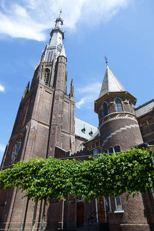 Boniface church with statue and blue sky in Leeuwarden capital of Friesland on sunny summer day behind trees