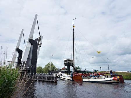 古い典型的な木造帆船オープン跳ね橋近くオランダ フリースラント州でスネークの近くの湖の航行の休暇に多くの子供たちと 報道画像