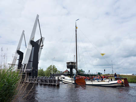 Old typical wooden sailing vessel with many children on sailing vacation on lake near Sneek in dutch province of friesland near open drawbridge