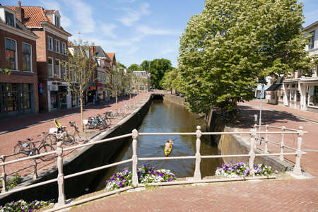 Leeuwarden, Netherlands, 11 june 2017: man in canoe passes colorful flowers on bridge in centre of old historic town leeuwarden in the netherlands