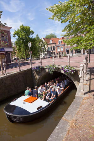 Leeuwarden, Netherlands, 11 june 2017: boat full of tourists passes colorful flowers on bridge in centre of old historic town leeuwarden in the netherlands