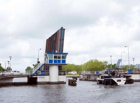 boat in european cultural capital 2018 Leeuwarden enters open drawbridge in the dutch province of friesland