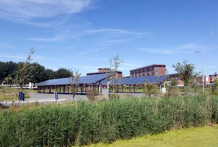 zonnepanelen op het dak van de parkeerplaats op de waterkampus Leeuwarden in nederland onder de blauwe hemel