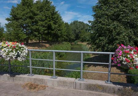 bridge over brook with flowers in countryside near Gooreind north of antwerp in belgium