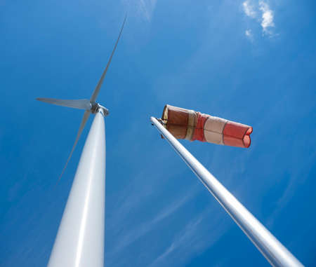 red and white windbag and wind turbine against background of blue sky Stock Photo