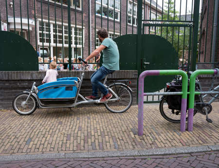 delft, netherlands, 30 june 2017: father waits with cargo bike at kindergarten in dutch town of delft