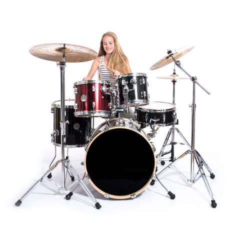 drumset: Young blonde caucasian teenage girl plays the drums in studio against white background Stock Photo