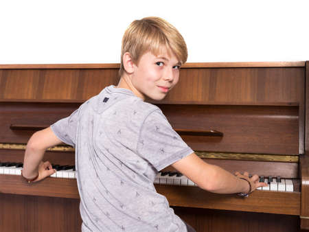 young blond caucasian teen boy plays the piano Reklamní fotografie