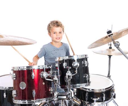 jonge blonde blanke jongen speelt drums in de studio tegen een witte achtergrond Stockfoto
