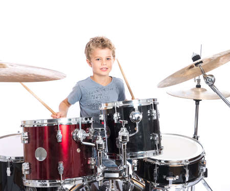 young blond caucasian boy plays drums in studio against white background