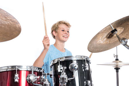 blond teen boy in blue plays drums at drumkit in studio against white background