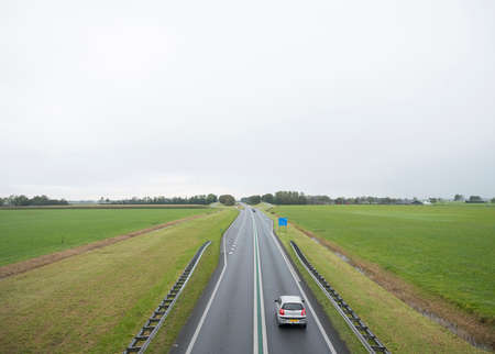 main road N46 north of groningen city between green meadows in the north of the netherlands