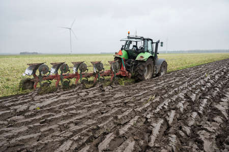 freshly plowed land and tractor with plough in dutch field end of autumn in the neth