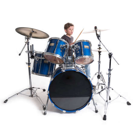 young blond boy at drum kit in studio against white background Stock Photo
