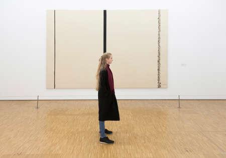 パリの博物館センターポンピドゥーでバーネットニューマンによる絵画の前の女の子