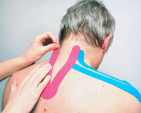 female physiotherapist applies tape on back of older grey haired caucasian man