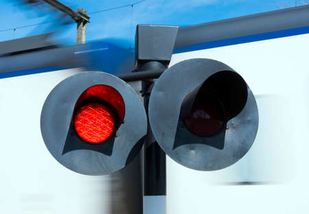 flashing red lights while white train passes railway crossing Archivio Fotografico