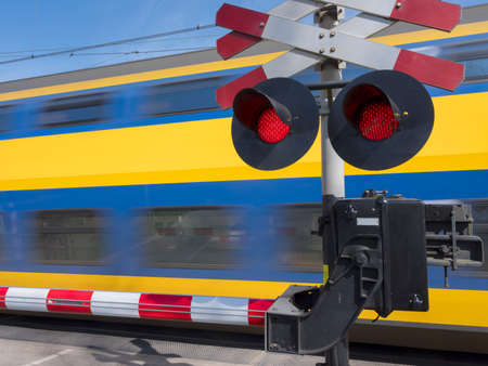 flashing red lights while blue and yellow train passes railway crossing Foto de archivo - 103271373