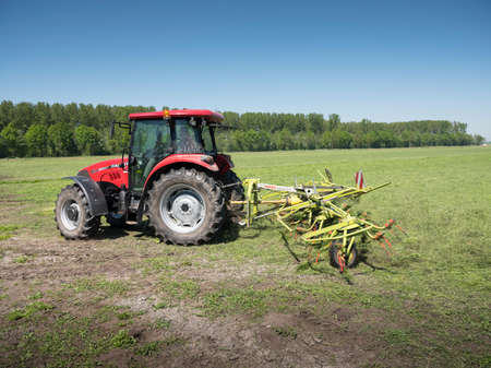 Meerkerk, Netherlands, 9 may 2018: tractor and grass turner work in dutch meadow in the province of south holland in the netherlands on sunny day Editorial